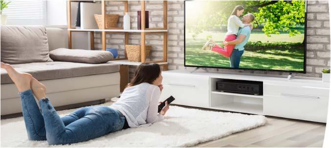Frau mit Fernseher im Wohnzimmer.