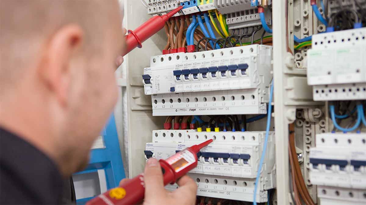 Ein Auszubildender beim Überprüfen eines Sicherungskastens auf Stromspannungen