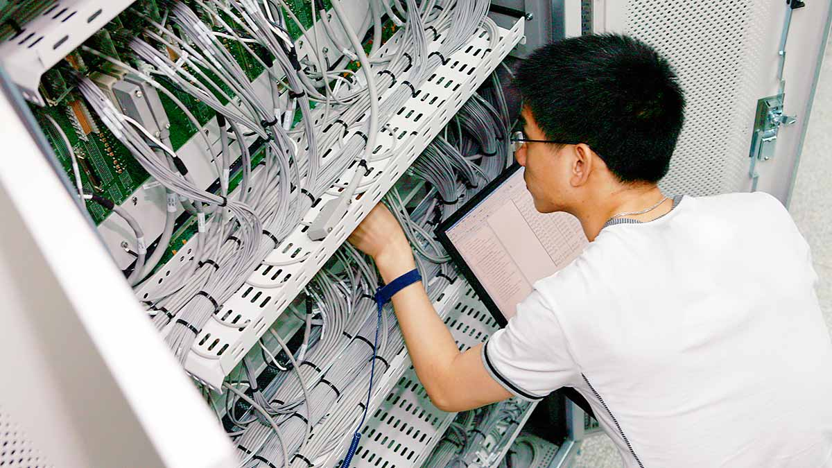 Ein Auszubildender beim Arbeiten in einem Serverschrank